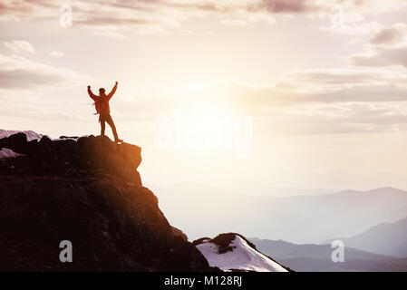Man in winner pose at mountain top against mountains and sunset - Stock Photo