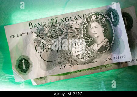 British One Pound notes, displayed on a green illuminated background. - Stock Photo