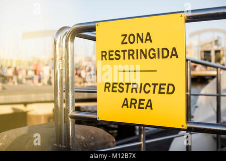 Restricted area signboard, written in Spanish and English. - Stock Photo