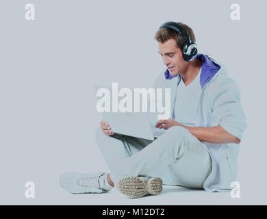 Young man listening to music from his laptop. - Stock Photo