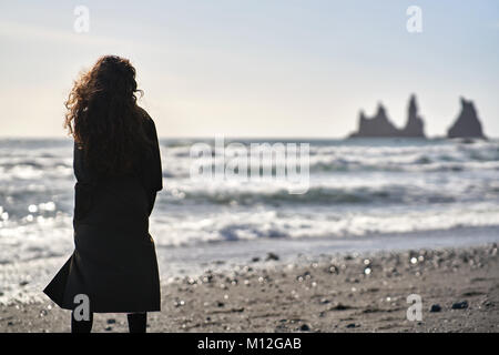 Woman stands on the black sand beach on the background of the stormy sea and rocks in Iceland.She wears a dark cloak - Stock Photo