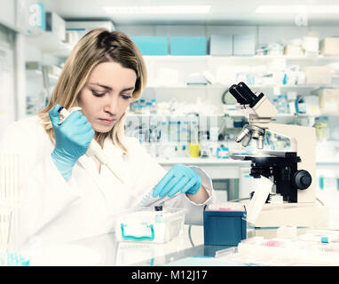 Young female tech or scientist loads liquid sample into test tube with plastic pipette. Shallow DOF, focus on the - Stock Photo