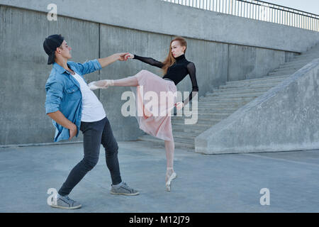 A slender ballerina dances with a modern dancer. Date of lovers. Performance in the streets of the city. - Stock Photo