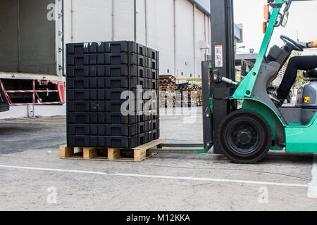 The worker loading pallet with a forklift into a truck. - Stock Photo