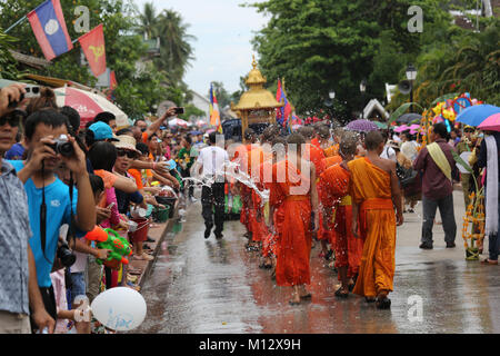 Watering the monks at Pi Mai Lao the Lao New Year Festival in UNESCO World Heritage Town of Luang Prabang, Laos, - Stock Photo