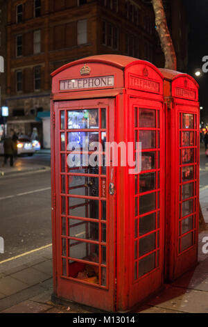 Red Telephone Box in the night in London with light reflections. - Stock Photo