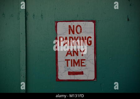 Rustic Sign No Parking Any Time with green background - Stock Photo