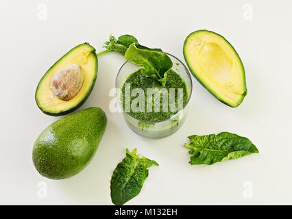 Glass with fresh green smoothie from spinach and avocado - Stock Photo