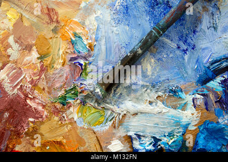 Vibrant colourful artists oil paint palette and well used brush. Shallow depth of field. - Stock Photo