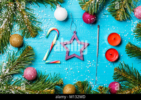Image of blue wooden table with spruce branches, figures from caramel, candles, Bengal lights, colorful balls - Stock Photo