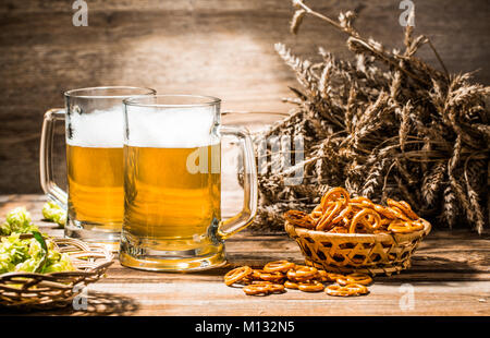 Two mugs of foam beer stand on wooden table with pretzels, wheat and hops - Stock Photo