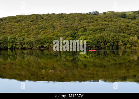 A couple pass in a canoe on Coniston Water on a dead calm early autumn morning in the Lake District, Cumbria, UK - Stock Photo
