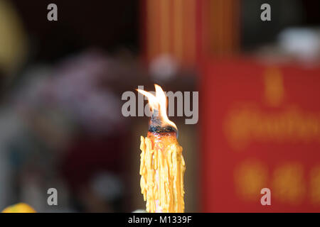 A candle burn in the temple in Bangkok, Thailand - Stock Photo
