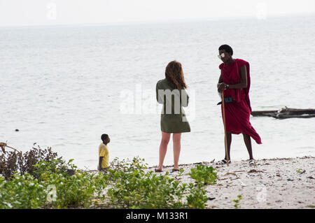 Massi man in traditional red cloak chats with a European woman on the beach in Jambiani Zanzibar Tanzania with a - Stock Photo