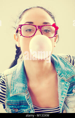 Young woman blowing bubblegum, intentionally toned. - Stock Photo