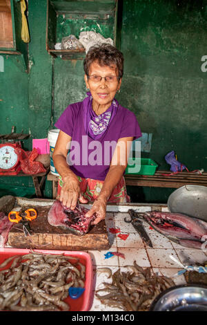 A senior age Filipino woman works in her fish stall splitting Bangus, a staple food fish, in the market at  Barretto, - Stock Photo