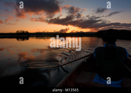 Finnish landscapes: Man rowing a row boat with oars on a calm lake in a beautiful sunrise, Finland - Stock Photo
