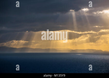 Sunrays bursting through dense sheet of rain clouds over sea water at sunset - Stock Photo