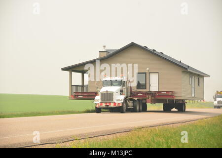 Moving a whole house on the back of a truck in the countryside of Canada. - Stock Photo