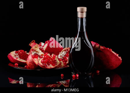 Ripe pomegranate and a bottle of juice on black background - Stock Photo