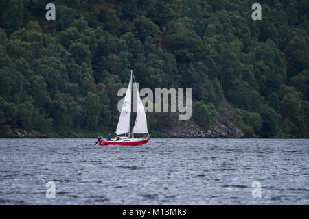With steep wooded hillside beyond, a small red boat with 2 sails, is sailing on the water of Ullswater lake - Lake - Stock Photo