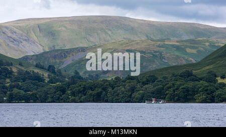 Passenger steamer boat travelling on the lake water, is overshadowed by scenic, towering hills & uplands - Lake - Stock Photo