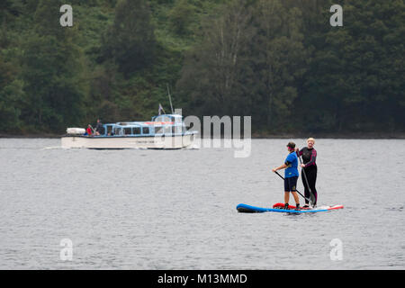 2 females stand on paddleboards on Coniston Water while people on Launch boat cruise trip are sailing beyond - Lake - Stock Photo