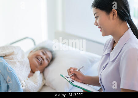 Asian nurse checking up the history of the disease elderly patient lying in bed. Nurse cares for a elderly woman. - Stock Photo