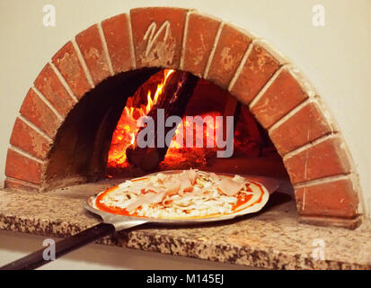 Europe,Italia,Pizzeria,Campania,Naples,Chef pulling pizza from oven - Stock Photo
