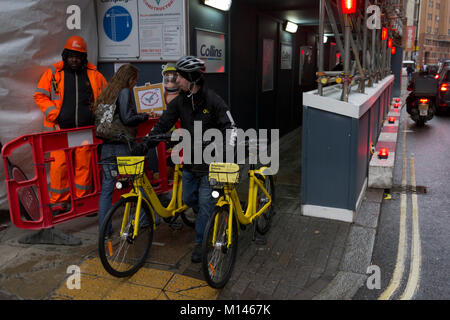 An Ofo employee pushes two rental bikes along a street, 24th January 2018, in London, England. ofo is a Beijing - Stock Photo