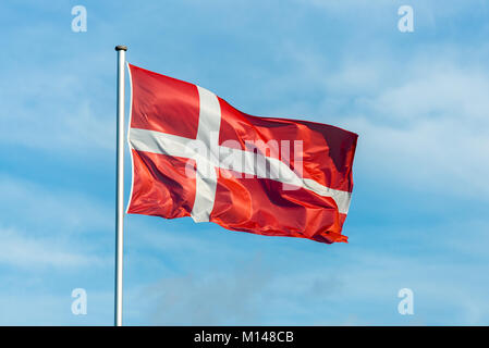 Closeup of single danish flag waving in the wind in front of blue sky - Stock Photo