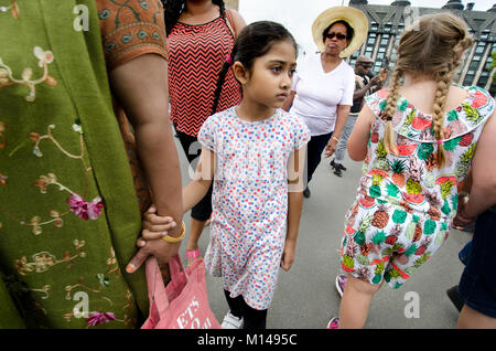 London, England, UK. Young Asian girl holding her mother's hand on Westminster Bridge - Stock Photo
