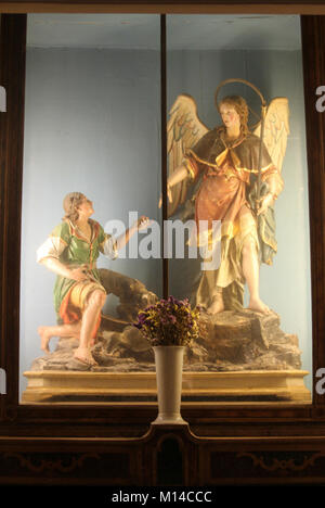 Wooden statues of angel giving hand to man in glass display in the Amalfi Cathedral, Amalfi, Italy. - Stock Photo