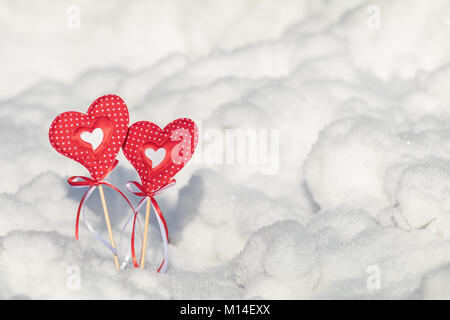 Beautiful valentine holiday background with two checkered hearts on cane, white snow surface. - Stock Photo