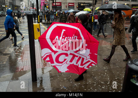 A lady carrying a Virgin Active brolly which has caught in the wind as Storm Georgina swept across parts of Britain - Stock Photo