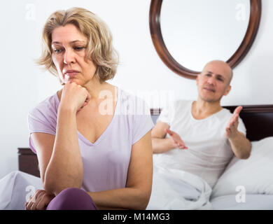 Frustrated mature wife and husband having serious conflict in bedroom - Stock Photo