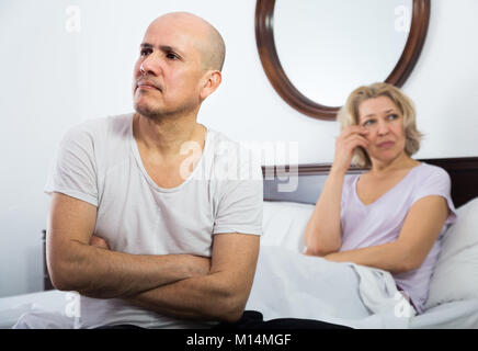 Frustrated aged man and his wife sorting out relationships in bed - Stock Photo