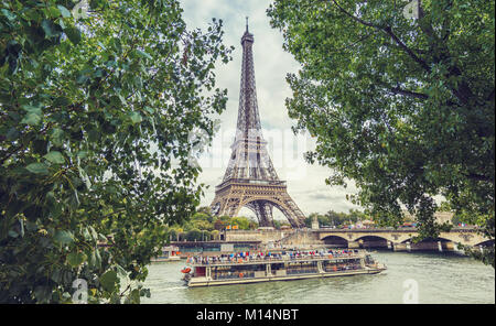 View from the Seine with tourist ship to the eiffel tower in paris. - Stock Photo