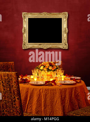Luxurious festing table against Red textured wall and golden wooden frame hanging - Stock Photo