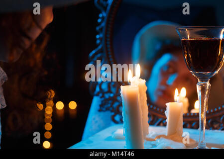 mirror with blurred female face candles and red wine - Stock Photo