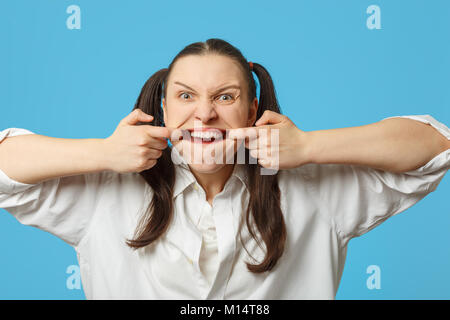 fun woman grimacing shows her teeth on blue background - Stock Photo