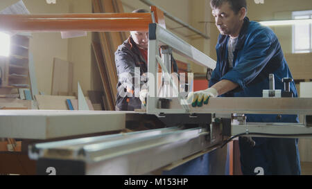Workers at factory are cutting wooden fragment on electric saw at furniture industry - Stock Photo