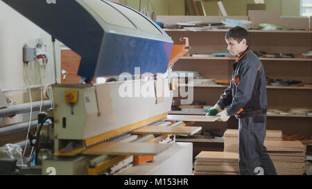 Worker carpenter handles wooden furniture parts on the machine on the factory - Stock Photo