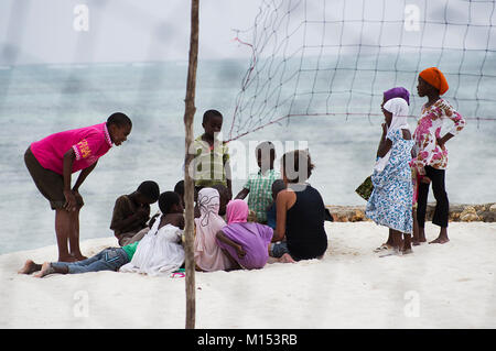 Local children in Zanzibar having a discussion on the white sandy beach in Nungwi, barefoot and wearing colourful - Stock Photo