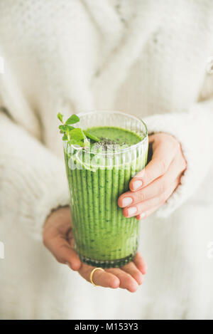 Healthy vegan breakfast. Matcha green smoothie with chia seeds and mint in hands of woman wearing white woolen sweater. - Stock Photo