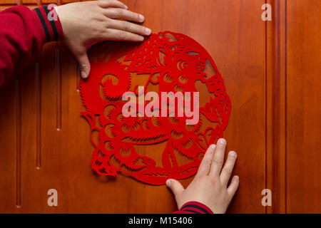 man sticking a Chinese New Year of the Dog 2018 to a door - Stock Photo
