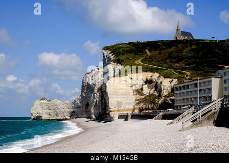 View of Chapelle Notre Dame de la Garde on the hilltop above the white chalk cliff and beach of the coast at Etretat, - Stock Photo