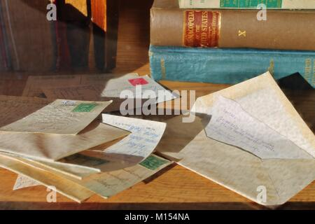 pile of old stamped letters and envelopes with antique books in background - Stock Photo