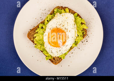 Fried Egg Sunny Side Up on Crushed Avocado And Rye Bread Open Faced Sandwich Against A Blue Background - Stock Photo