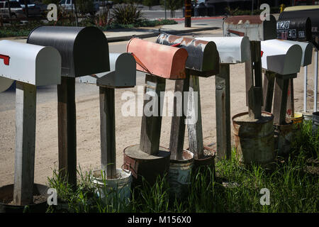 A row of many old metal mail boxes on top of wooden posts set into tubs of cement along a rural road, viewed from - Stock Photo